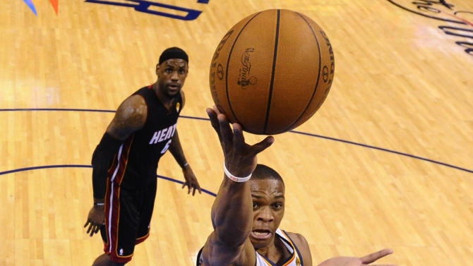 Oklahoma City Thunder point guard Russell Westbrook (0) shoots over Miami Heat small forward Shane Battier  as small forward LeBron James  ooks on during the first half at Game 2 of the NBA finals basketball series, Thursday, June 14, 2012, in Oklahoma City. (AP Photo/Larry W. Smith, Pool)