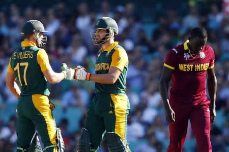 South Africa's AB de Villiers and team mate Rilee Rossouw celebrate a boundary as West Indies bowler Jerome Taylor reacts during their Cricket World Cup match at the SCG