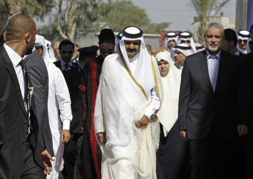 Gaza's Hamas prime minister Ismail Haniyeh, right, and Emir of Qatar Sheikh Hamad bin Khalifa al-Thani, center, walk together during a welcoming ceremony in Rafah, southern Gaza Strip, Tuesday, Oct. 23, 2012. The emir of Qatar received a hero's welcome in Gaza on Tuesday, the first head of state to visit the Palestinian territory since Islamist Hamas militants seized control there five years ago. He will deliver more than $250 million in aid, a move that will bolster Hamas and ease its international isolation.(AP Photo/ Mohammed Abed, Pool)