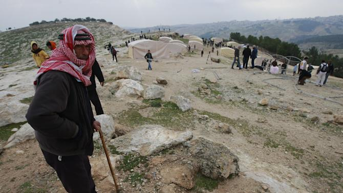 A Palestinian Bedouin man watches construction on the new 'outpost ' of Bab al-Shams (Gate of the Sun) in an area known as E1, near Jerusalem, Friday, Jan 11, 2013. Palestinian activists pitched tents in the West Bank on Friday to protest Israeli plans to build a large Jewish settlement on a key route through the territory. The E-1 settlement would block east Jerusalem from its West Bank hinterland — both territories captured by Israel during the 1967 Mideast war. (AP Photo/Majdi Mohammed)