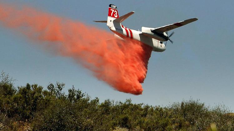 A firefighting aircraft drops fire retardant along a hill side near Thousand Oaks, Calif. on Thursday, May 2, 2013. A 2,000-acre blaze that began in the Camarillo area along U.S. 101 in Ventura County was uncontained. It prompted the evacuation of a Thousand Oaks neighborhood and the campus of California State University, Channel Islands. At least a half-dozen RVs burned in a parking area enclosed by brushy hills. Embers scattered along ridges and into neighborhoods abutting the brush lands and smoke streamed for miles. More than 200 firefighters were aided by water- and fire retardant-dropping aircraft. (AP Photo/Nick Ut)