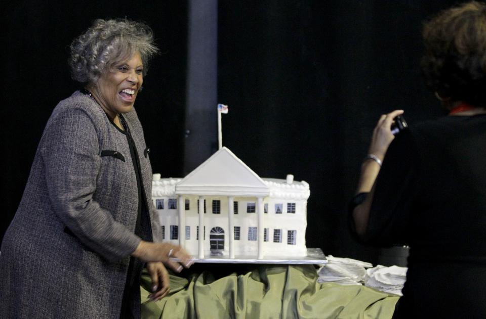Jerry Banks, left, the aunt of actor Tyler Perry, reacts as she has her picture taken by Nena Bright, right, with a cake depicting the White House as President Barack Obama speaks during a fundraiser at Perry's film studio Friday, March 16, 2012, in Atlanta. (AP Photo/David Goldman)