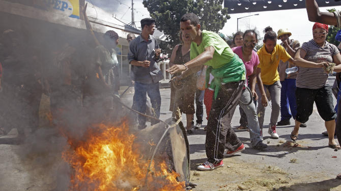 A protesting farm worker puts grass on a fire as he and others protest in the town of Swellendam,  South Africa, Thursday, Nov. 15, 2012. Farm workers angered over their minimum daily wages launched a second day of violent protests in the nation's Western Cape, setting fires and marching through the countryside. (AP Photo/Schalk van Zuydam)