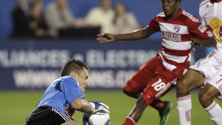New York Red Bulls goalkeeper Frank Rost, left, blocks a shot on gaol as FC Dallas midfielder Marvin Chavez (18) pressures in the first half of an MLS Cup first-round soccer match on Wednesday, Oct. 26, 2011, in Frisco, Texas. (AP Photo/Tony Gutierrez)