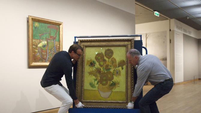 "Curators are putting Vincent van Gogh's famous ""Sunflowers"" painting onto a felt-lined carrier trolley at the Van Gogh Museum in Amsterdam, Netherlands, Sunday, Sept. 23, 2012. While the museum closes for seven months for renovations, 75 works by the Dutch painter will be displayed instead across town at The Hermitage, an Amsterdam satellite of the Russian state museum. The tricky process of transporting the artworks under police escort began immediately after the last visitors left the museum Sunday evening and carried on through the night into Monday morning. The Van Gogh Museum reopens April 25, 2013. (AP Photo/Cris Toala Olivares)"