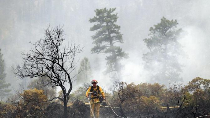 FILE - This Aug. 4, 2014 file photo shows a a firefighter with the Anderson, Calif., Fire Protection District dousing hot spots left behind by the Eiler Fire near Burney, Calif. The U.S. Forest Service will soon have to tap into programs designed to prevent wildfires so that it can meet the expenses of fighting this summer's round of fires. Agriculture Secretary Tom Vilsack said Tuesday that about $400 million to $500 million in projects will have to be put on hold in what has become a routine exercise toward the end of the fiscal year. He predicted that the money set aside strictly for firefighting will have run dry by the end of August. (AP Photo/Marcio Jose Sanchez, File)
