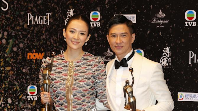 """Chinese actress Zhang Ziyi, left, and actor Nick Cheung Ka-fai pose after winning the Best Actress award for her movie """"The Grandmaster"""" and Best Actor awards for his movie """"Unbeatable"""" at the 33rd Hong Kong Film Awards in Hong Kong Sunday, April 13, 2014. (AP Photo/Kin Cheung)"""