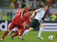 Germany&#39;s Bastian Schweinsteiger is followed by Portugal&#39;s Portugal&#39;s Helder Postiga, left, during the Euro 2012 soccer championship Group B match between Germany and Portugal in Lviv, Ukraine, Saturday, June 9, 2012. (AP Photo/Martin Meissner)