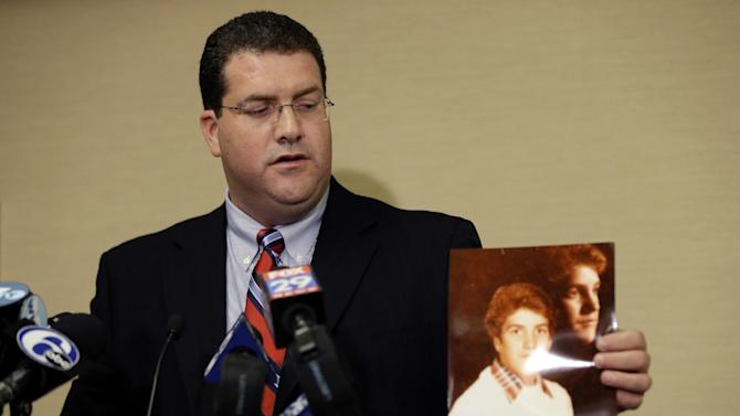 Plaintiff Michael McDonnell displays a photo of himself as a young man during a news conference Tuesday, Sept. 18, 2012, in Philadelphia. Nine plaintiffs allege in civil lawsuits filed Tuesday that the Archdiocese of Philadelphia covered up child sex assault allegations made against seven Roman Catholic priests. (AP Photo/Matt Rourke)