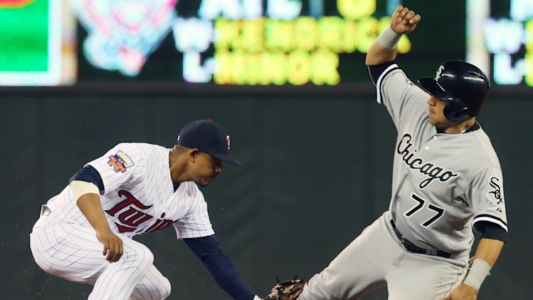 Chicago White Sox's Carlos Sanchez, right, is tagged out by Minnesota Twins shortstop Eduardo Escobar on a steal attempt in the ninth inning of a baseball game, Tuesday, Sept. 2, 2014, in Minneapolis. The White Sox won 6-3 in 10 innings. (AP Photo/Jim Mone)
