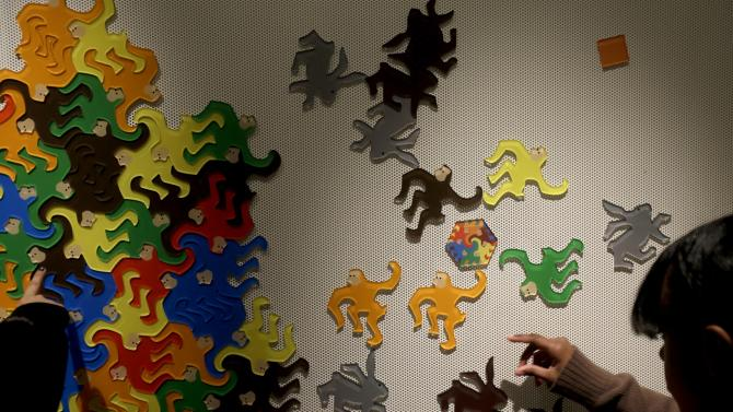 """Students play with interlocking shapes at a """"Tessellation Station"""" at the new National Museum of Mathematics in New York, Monday, Dec. 17, 2012. The museum is aimed at kids aged 8 to 13, and curators have given the place a playground feel. The 40 exhibits include a """"wall of fire"""" made up of laser lights that teaches kids about geometry and a square-wheeled tricycle that still manages to produce a smooth ride thanks to a wavy track. (AP Photo/Seth Wenig)"""