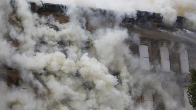 Smoke billows out from a fire at a historic row in downtown Louisville, Ky., Monday, July 6, 2015. Some of the Whiskey Row properties were built in the 1850s and used for warehousing barrels of whiskey produced at area distilleries. (Pat McDonogh/The Courier-Journal via AP) NO SALES; MAGS OUT; NO ARCHIVE; MANDATORY CREDIT