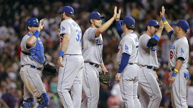 Los Angeles Dodgers starting pitcher Clayton Kershaw, third from left, celebrates with teammates after pitching a four-hitter against the Colorado Rockies in a baseball game Tuesday, July 2, 2013, in Denver. The Dodgers won 8-0. (AP Photo/Barry Gutierrez)