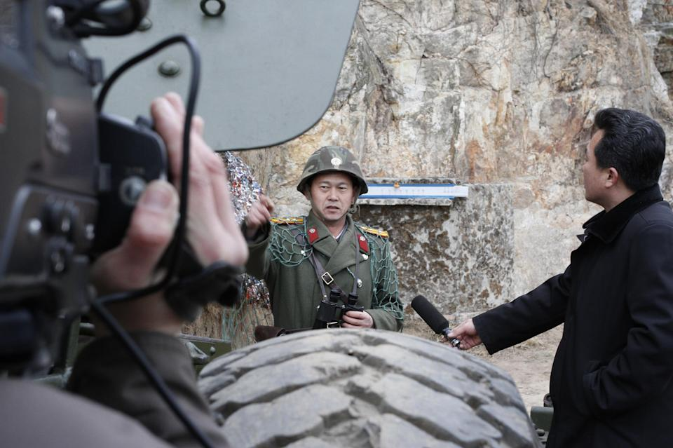 In this Sunday March 4, 2012 photo, North Korean journalists interview a North Korean soldier during military exercises at a military base on North Korea's southwest coast, opposite South Korea's Baengnyeong Island. (AP Photo/Kim Kwang Hyon)