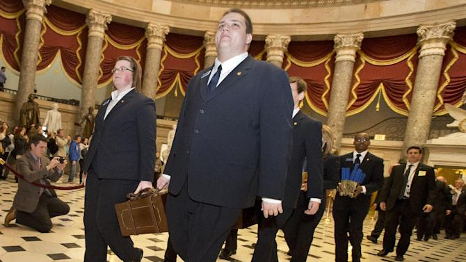Pages lead a Senate procession carrying two boxes holding Electoral College votes through Statuary Hall to the House Chamber on Capitol Hill on Capitol Hill in Washington, Friday, Jan. 4, 2013, for the counting of the votes in the presidential election. A tally of the U.S. Electoral College vote affirmed President Barack Obama's re-election.  (AP Photo/Jacquelyn Martin)
