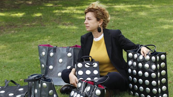 This Oct. 24, 2012 photo shows Ilaria Venturini Fendi, a member of the famous fashion family, posing with bags from her Carmina Campus fashion project that produces bags from repurposed materials in Dallas.  The bags shown are made of garbage bags and soda cans. (AP Photo/LM Otero)