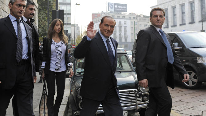 FILE- In this Oct. 19, 2012 file photo former Italian Premier Silvio Berlusconi salutes as he arrives for a court hearing in Milan. A court in Italy has convicted, Friday, Oct. 26, 2012, former Premier Silvio Berlusconi of tax fraud and sentenced him to four years in prison. In Italy, cases must pass two levels of appeal before the verdicts are final. Berlusconi is expected to appeal. (AP Photo/Gian Mattia D'Alberto, Lapresse, File) ITALY OUT
