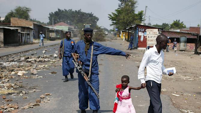 A policeman gestures as a man walks with his daughter during a protest against President Pierre Nkurunziza's decision to run for a third term in Bujumbura