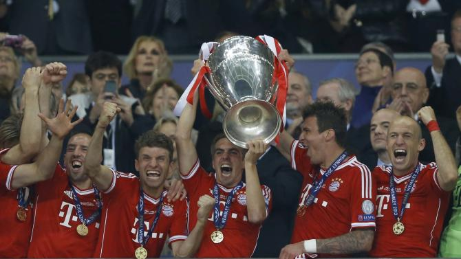 Bayern's Philipp Lahm holds up the trophy after his side won the Champions League Final soccer match against Borussia Dortmund at Wembley Stadium in London, Saturday May 25, 2013.  (AP Photo/Kirsty Wigglesworth)