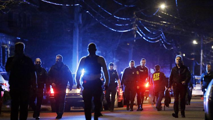 Police officers walk near a crime scene Friday, April 19, 2013, in Watertown, Mass. A tense night of police activity that left a university officer dead on campus just days after the Boston Marathon bombings and amid a hunt for two suspects caused officers to converge on a neighborhood outside Boston, where residents heard gunfire and explosions.(AP Photo/Matt Rourke)