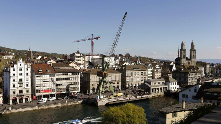 A tourist boat sails past a dockside crane on the banks of the Limmat river in Zurich