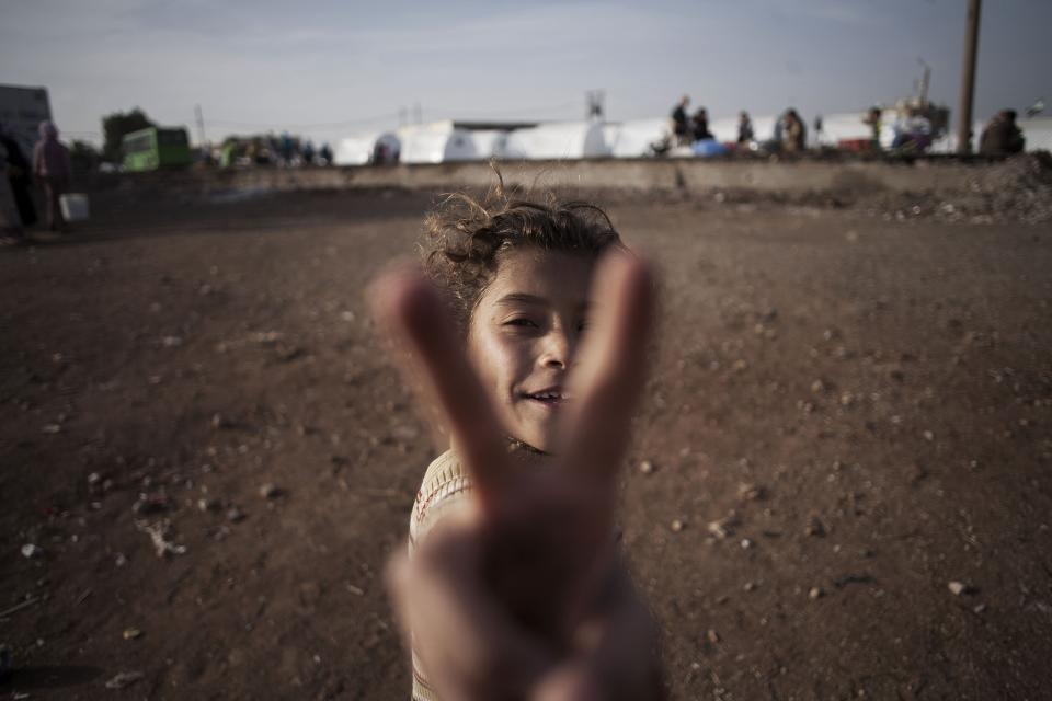 A Syrian girl, who fled her home with her family due to fighting between government forces and rebels, flashes the victory sign at a refugee camp near the Turkish border, Azaz, Syria, Sunday, Oct. 7, 2012. (AP Photo/ Manu Brabo)