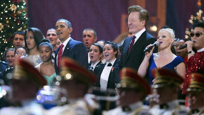 President Barack Obama, third from left, with his daughters Malia Obama, from left, and Sasha Obama, join host, from third right to right, Conan O'Brien, singer Megan Hilty, South Korean rapper PSY and other performers, during the Annual Christmas in Washington presentation at the National Building Museum in Washington, Sunday, Dec. 9, 2012. (AP Photo/Manuel Balce Ceneta)