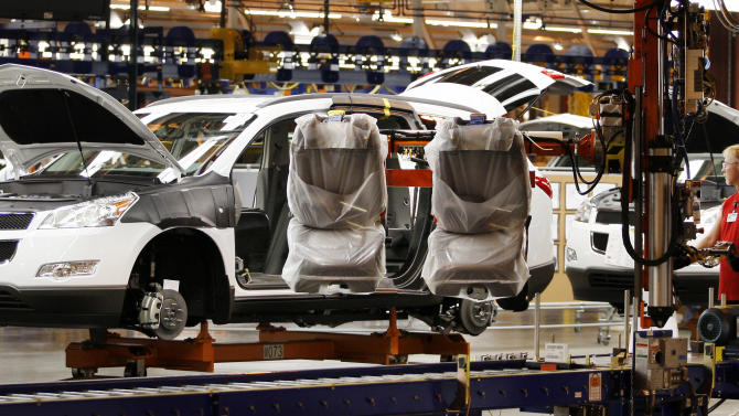 FILE - In this Oct. 3, 2008 file photo, assembly line worker Melvin Matthews, right, installs front seats in a Chevrolet Traverse at the General Motors Spring Hill Manufacturing Plant in Spring Hill, Tenn. General Motors announced Tuesday, Aug. 6, 2013, that it is spending another $167 million at the factory so it can build two new midsize vehicles. (AP Photo/Bill Waugh, File)