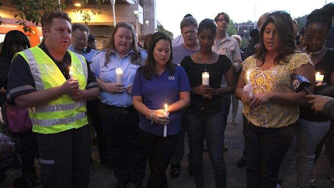 Mourners hold candles to honor the memory of two workers who were killed during a train accident in Walnut Creek, Calif., Sunday, Oct. 20, 2013. Two federal accident investigators arrived in the San Francisco Bay area on Sunday to examine the deaths of two transit workers who on Saturday, were struck by an out-of-service commuter train performing routine maintenance against the backdrop of a labor strike. (AP Photo/Eric Slomanson)