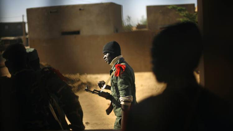 FILE In this Feb. 7, 2013 file photo, a Malian soldier walks in Gao, northern Mali. Timbuktu has been hit by a prolonged battle between Islamic extremists and the Malian and French armies, residents and a Malian military spokesman said Sunday, March 31. The attack started Saturday night at about 10 p.m. local time when a jihadist suicide bomber blew himself up at a Malian military checkpoint at the western entrance to Timbuktu, and fighting continued Sunday, according to Capt. Samba Coulibaly, spokesman for the Malian military in Timbuktu. (AP Photo/Jerome Delay, File)
