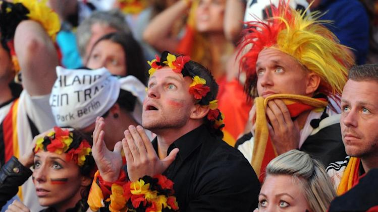 German soccer fans react as they watch a live broadcast of the final match between Germany and Argentina at the soccer World Cup 2014 in Rio de Janeiro, Brazil, at a public viewing area called 'Fan Mile' in Berlin, Sunday, July 13, 2014. . (AP Photo/dpa, Britta Pedersen)