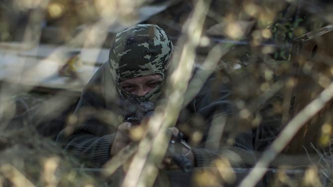 """An American who calls himself """"Hunter"""" aims his rifle near the town of Yasynuvata"""