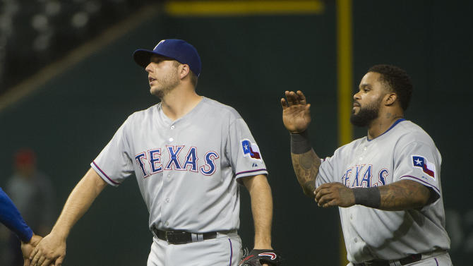 Texas Rangers' Shawn Tolleson, left, and Prince Fielder react after the Rangers defeated the Cleveland Indians in a baseball game in Cleveland, Tuesday, May 26, 2015. The Rangers won 4-3. (AP Photo/Phil Long)
