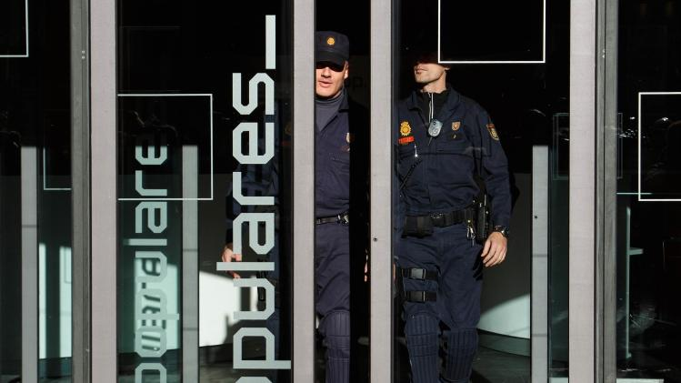 Police officers leave the ruling People's Party headquarters in Madrid