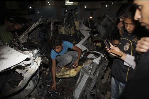 Palestinian boy inspects a destroyed vehicle following an Israeli air strike in Rafah
