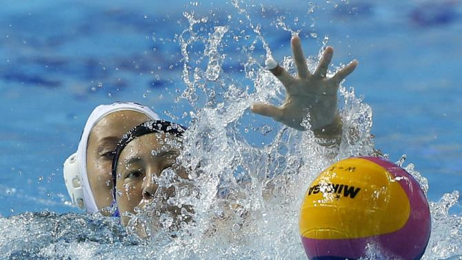 Japan's Nakano fights for the ball with Kazakhstan's Alexandrova during their Women's Single Round Robin water polo match at the Dream Park Aquatics Centre during the 17th Asian Games in Incheon