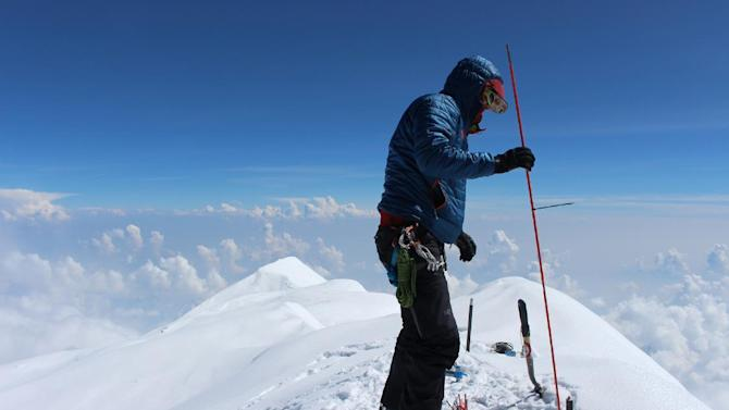 In this June 24, 2015, photo provided by Compass Data/USGS, Blaine Horner of CompassData probes the snow pack at the highest point in North America along with setting up Global Position System equipment for precise summit elevation data on top of Denali in Denali National Park, Ak. The U.S. Geological Survey announced Wednesday, Sept. 2, 2015, that the new official height for Denali has been measured at 20,310 feet, just 10 feet less than the previous elevation of 20,320 feet which was established using 1950's era technology. (Blaine Horner/Compass Data/USGS via AP)