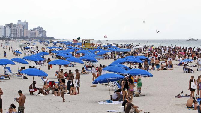 FILE - In this Friday, May 28, 2010, file photo, tourists and local residents enjoy a day the the beach as Memorial Day weekend begins in the South Beach area of Miami, Beach, Fla. With a little advance planning, and some insider tips, summer vacations can be a lot less expensive. (AP Photo/Alan Diaz, File)