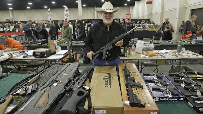 "FILE - In this Jan. 6, 2013 file photo, Ken Haiterman, of Pioneer Market, holds a CMMG 5.56mm AR 15 during the 2013 Rocky Mountain Gun Show in Sandy, Utah. A bipartisan quartet of senators, including two National Rifle Association members and two with ""F"" ratings from the potent firearms lobby, are quietly trying to reach compromise on expanding the requirement for gun-sale background checks. (AP Photo/Rick Bowmer, File)"