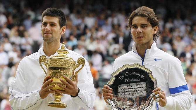 Serbia's Novak Djokovic and Spain's Rafael Nadal, right, hold their trophies after Novak Djokovic defeated Rafael Nadal in the men's singles final at the All England Lawn Tennis Championships at Wimbledon, Sunday, July 3, 2011. (AP Photo/Kirsty Wigglesworth)