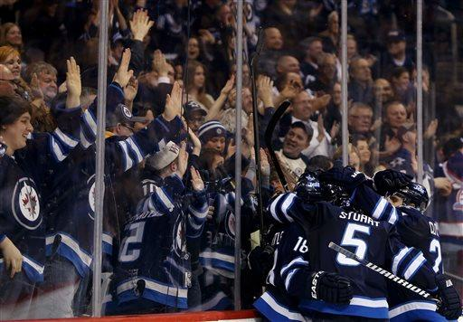 Winnipeg Jets players celebrate after Andrew Ladd scored against the Buffalo Sabres during the second period of their NHL hockey game in Winnipeg, Manitoba, Tuesday, April 9, 2013