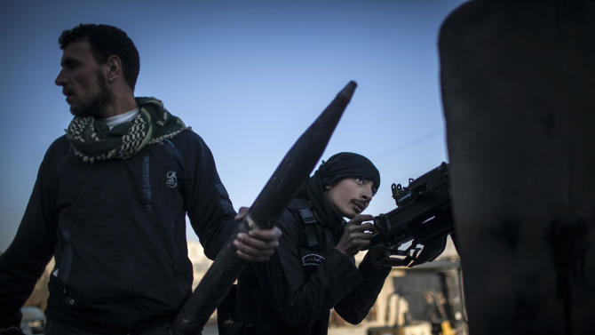 A Free Syrian Army fighter aims his weapon during clashes with government forces in Aleppo, Syria, Tuesday, Jan. 15, 2013. Two explosions struck the main university in the northern Syrian city of Aleppo on Tuesday, causing an unknown number of casualties, state media and anti-government activists said. (AP Photo/Andoni Lubaki)
