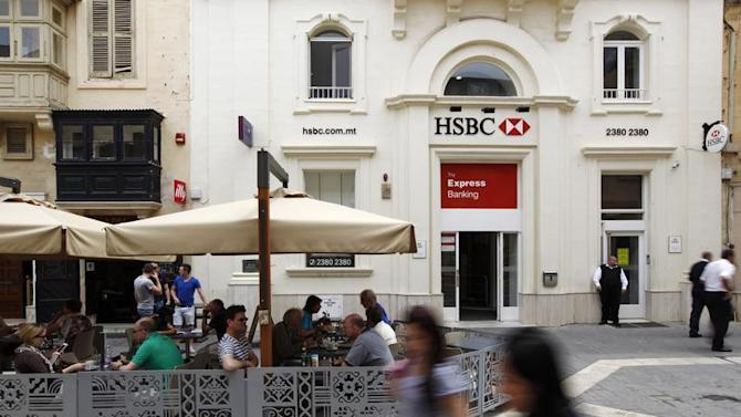 People sit in an outdoor coffee shop in front of an HSBC bank branch in Valletta