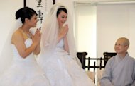 Taiwanese women Fish Huang (L) and her partner You Ya-ting accept the blessing from Master Shih Chao-hui during their same-sex Buddhist wedding ceremony in Taoyuan, on August 11. The two women tied the knot in Taiwan's first same-sex Buddhist wedding, a move rights groups hope will help make the island the first society in Asia to legalise gay marriage