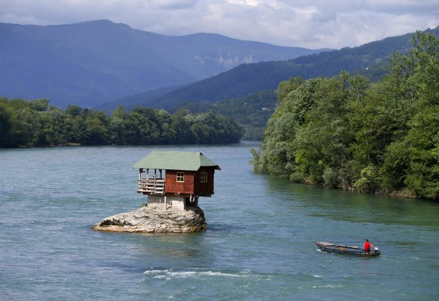 A man rows a boat near a house built on a rock on the river Drina near the western Serbian town of Bajina Basta