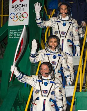 Russian astronaut Mikhail Tyurin holds the Olympic…