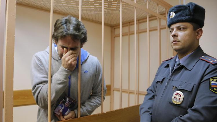 Greenpeace International activist Miguel Hernan Perez Orsi of Argentina, left, reacts to a verdict and holds a photo of his daughter in a cage at a court room during a hearing that's considering the investigators request to extend the detention of 30 members of the Arctic Sunrise Greenpeace International ship in St.Petersburg, Russia,Tuesday, Nov. 19, 2013. Miguel Hernan Perez Orsi was released on bail of 2 million rubles ($61,500). (AP Photo/Dmitry Lovetsky)