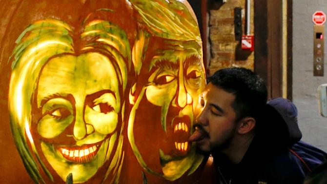 A man tries to lick a giant pumpkin with the faces of 2016 Democratic nominee Hillary Clinton and Republican presidential nominee Donald Trump at Chelsea Market in New York