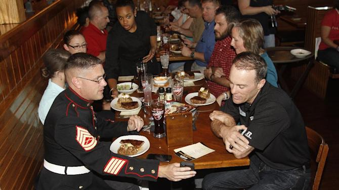 IMAGE DISTRIBUTED FOR OUTBACK STEAKHOUSE® - NASCAR driver Kevin Harvick dines with local military troops at a Greensboro, NC Outback Steakhouse® to celebrate Outback's partnership with Folds of Honor. Image released on Thursday, October 23, 2014. (Jim R. Bounds/AP Images for Outback Steakhouse®)