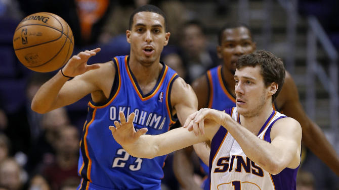 Phoenix Suns guard Goran Dragic, of Slovenia, passes as Oklahoma City Thunder guard Kevin Martin (23) defends during the first half of an NBA basketball game, Monday, Jan. 14, 2013, in Phoenix. (AP Photo/Matt York)